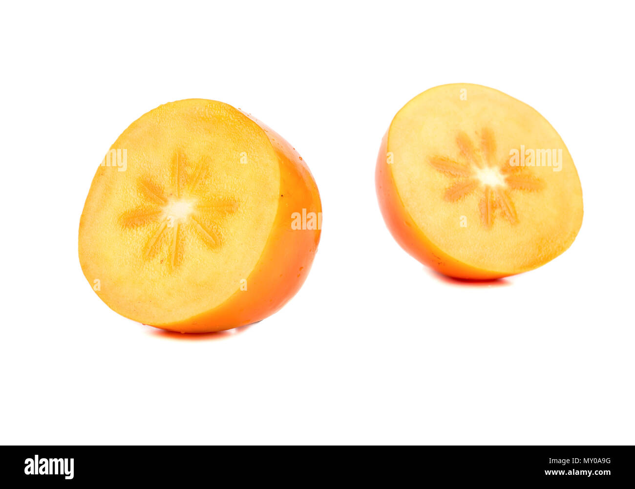 Ripe fruit of a persimmon cut into two halves on white background - Stock Image