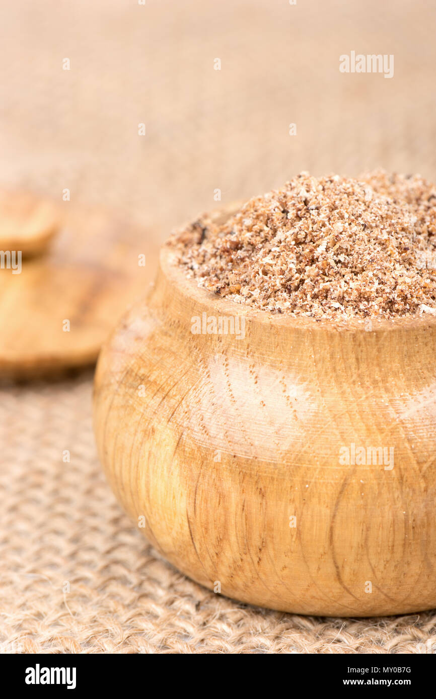 Spice nutmeg in the wooden jar on the burlap - Stock Image