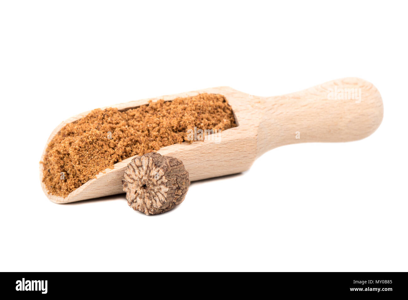 Nutmeg powder in the scoop with a half walnut on white background - Stock Image