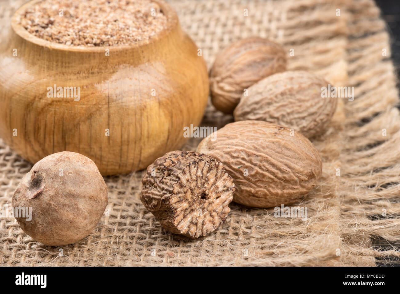 Jar with nutmeg powder and scattered with nuts on burlap - Stock Image