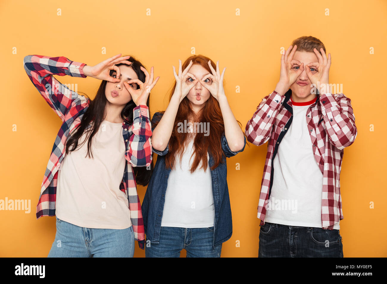 Group of happy school friends grimacing and having fun while standing together over yellow background - Stock Image
