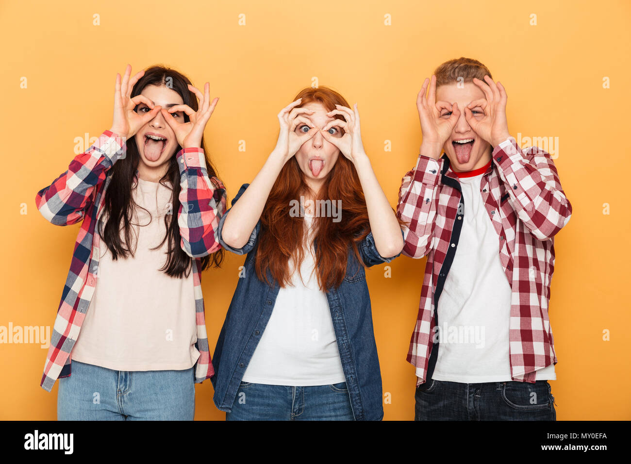 Group of funny school friends grimacing and having fun while standing together over yellow background - Stock Image