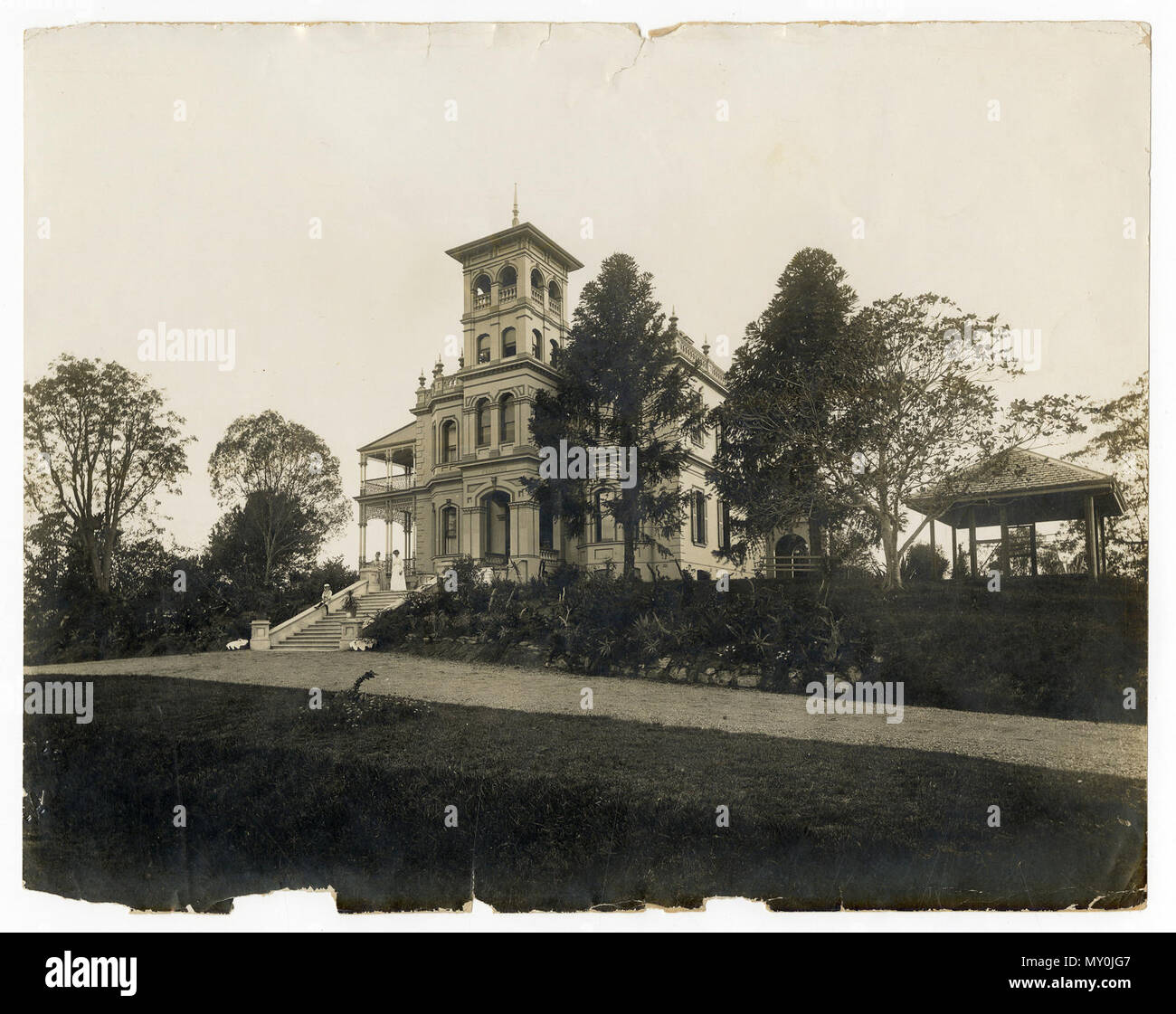 Government House, Fernberg Road, Paddington, c 1912. Johann Heussler, a wealthy Brisbane merchant purchases 22 acres of land from the Government in 1862 and made plans to build a house there. Local architect Benjamin Backhouse designed a house in 1865, to be constructed from stone excavated on site combined with a cement and lime mixture.  The Heussler family lived at Fernberg from 1865 until 1872 when the high cost of upkeep forces foreclosure on the property by the mortgagee.  Sir Arthur Palmer, Premier of Queensland (1870-1874), and later Lieutenant Governor resided in Fernberg from 1872 to - Stock Image