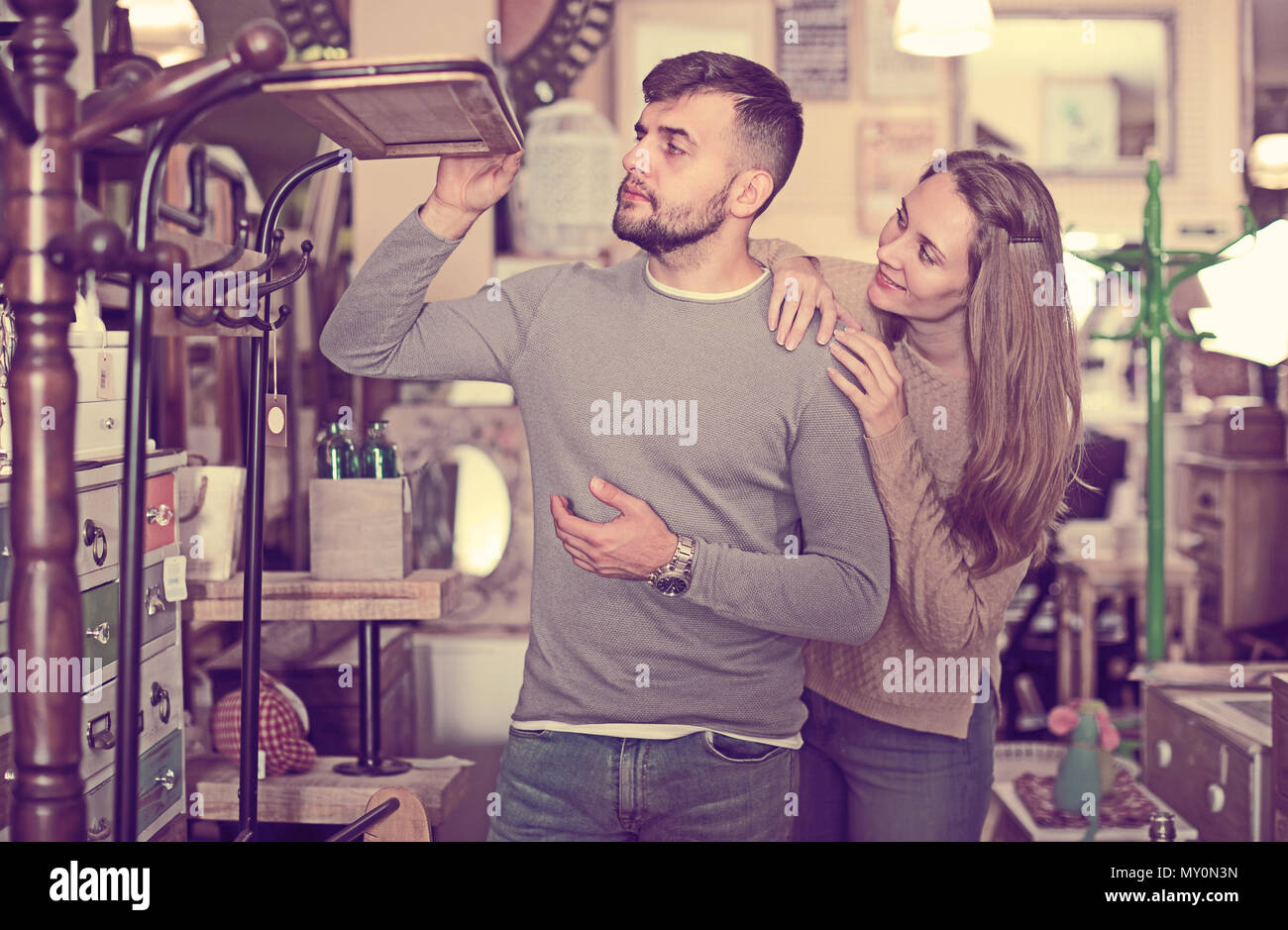 Loving couple looking for hallstand in shop of secondhand furniture - Stock Image