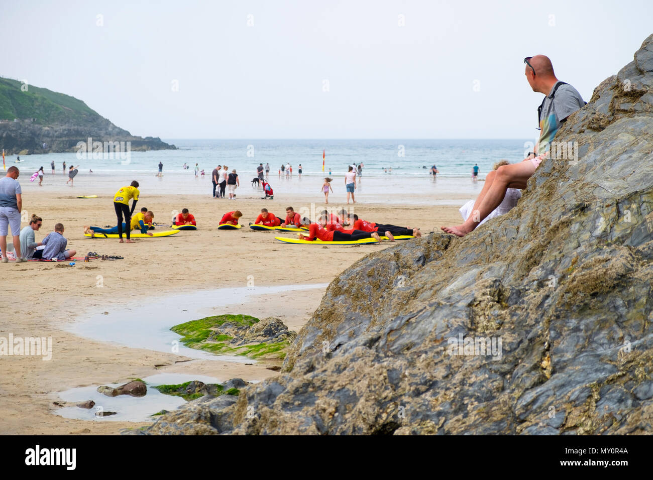 A man looks on as surf school lessons take place on the fistral beach, newquay, uk - Stock Image