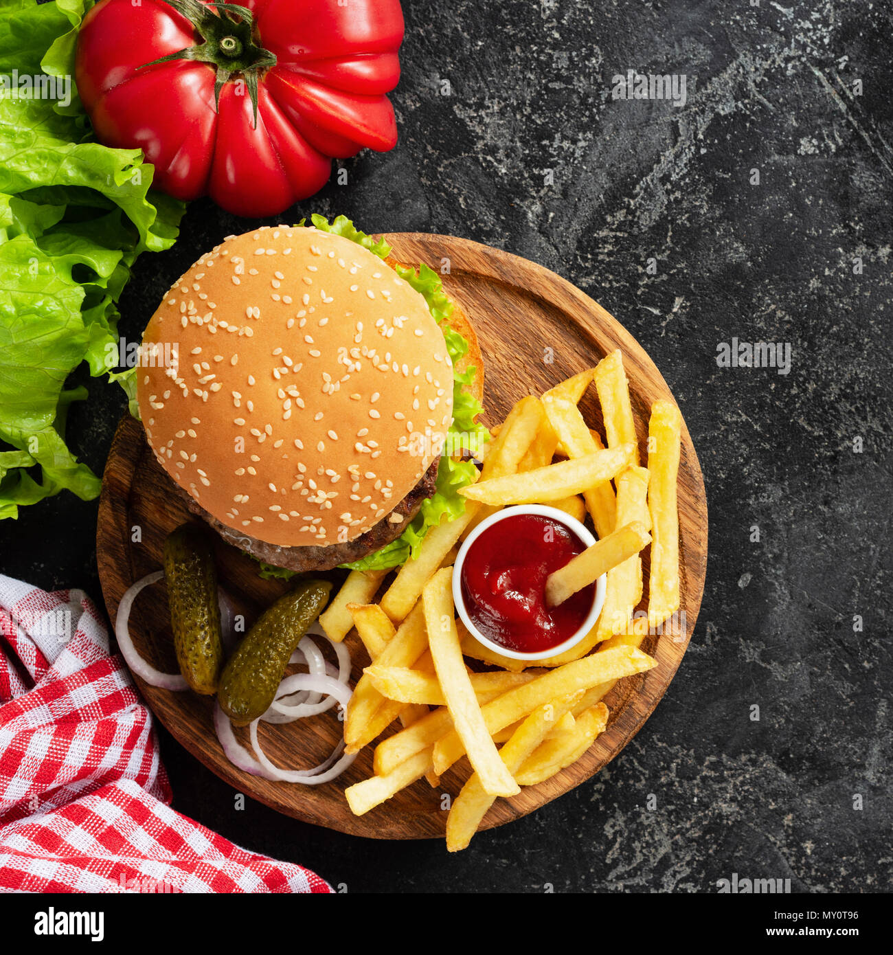 Hamburger, french fries, pickles and ketchup on wooden board. Fast food. Homemade burger and potato fries. Top view with copy space for text - Stock Image