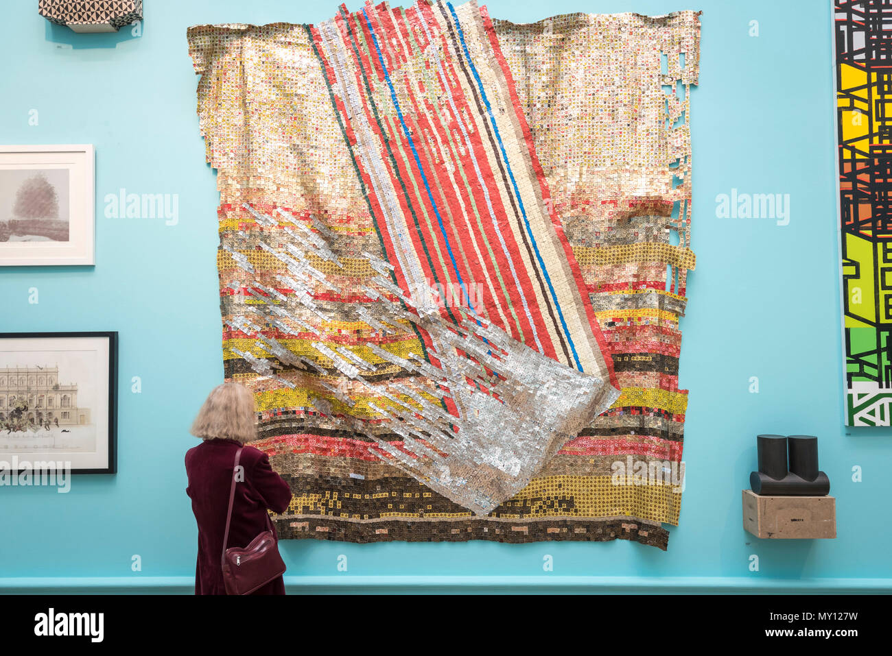 London, UK.  5 June 2018. A visitor views 'Change in Fortune' by El Anatsui Hon RA at the preview of the 250th Summer Exhibition at the Royal Academy of Arts in Piccadilly, which has been co-ordinated by Grayson Perry RA this year.  Running concurrently, is The Great Spectacle, featuring highlights from the past 250 years.  Both shows run 12 June to 19 August 2018. Credit: Stephen Chung / Alamy Live News - Stock Image