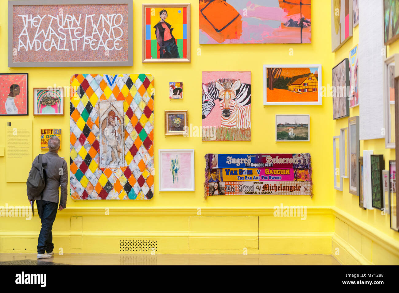 London, UK.  5 June 2018. A visitor views artworks in a vividly yellow painted gallery at the preview of the 250th Summer Exhibition at the Royal Academy of Arts in Piccadilly, which has been co-ordinated by Grayson Perry RA this year.  Running concurrently, is The Great Spectacle, featuring highlights from the past 250 years.  Both shows run 12 June to 19 August 2018.  Credit: Stephen Chung / Alamy Live News - Stock Image