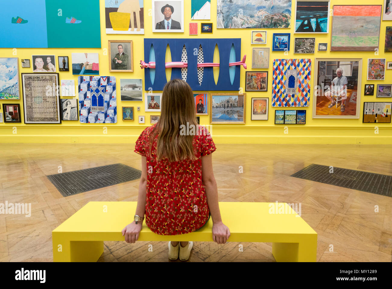 London, UK.  5 June 2018. A staff member sits amidst artworks in a vividly yellow painted gallery at the preview of the 250th Summer Exhibition at the Royal Academy of Arts in Piccadilly, which has been co-ordinated by Grayson Perry RA this year.  Running concurrently, is The Great Spectacle, featuring highlights from the past 250 years.  Both shows run 12 June to 19 August 2018.  Credit: Stephen Chung / Alamy Live News - Stock Image