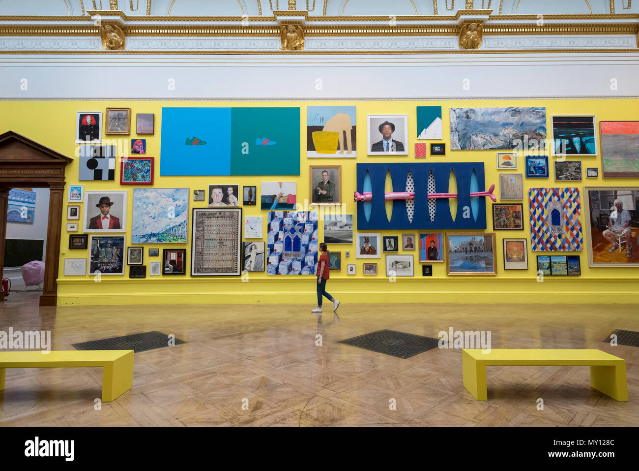 London, UK.  5 June 2018. A staff member walks amidst artworks in a vividly yellow painted gallery at the preview of the 250th Summer Exhibition at the Royal Academy of Arts in Piccadilly, which has been co-ordinated by Grayson Perry RA this year.  Running concurrently, is The Great Spectacle, featuring highlights from the past 250 years.  Both shows run 12 June to 19 August 2018.  Credit: Stephen Chung / Alamy Live News - Stock Image