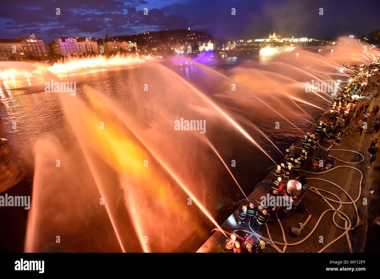 """Some 1,000 firefighters from across the country create a musical fountain on the Vltava River (Moldau) in Prague, during a rehearsal on Friday, June 1st, 2018, prior to the tomorrow's celebration of the 100th anniversary of Czechoslovakia's establishment. The fountain was be formed by both professional and voluntary firefighters using approximately 200 hose nozzles above the river in the centre of Prague, between Jirasek and Palacky bridges. """"A light concert"""" and """"a water ballet"""" using several thousand cubic metres of water was orchestrated in a single moment. Music as well as colour lights ac Stock Photo"""