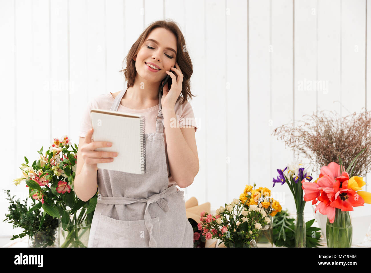 Young florist woman standing near table with different flowers in studio and calling to clients with notes in hand - Stock Image