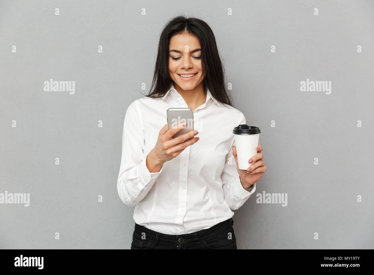 Photo of attractive business woman in formal wear holding mobile phone and takeaway coffee in hands isolated over gray background - Stock Image