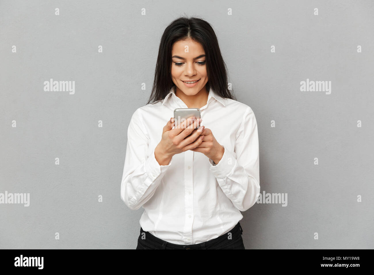 Photo of content young woman 30s in formal wear standing with smartphone in hands isolated over gray background - Stock Image