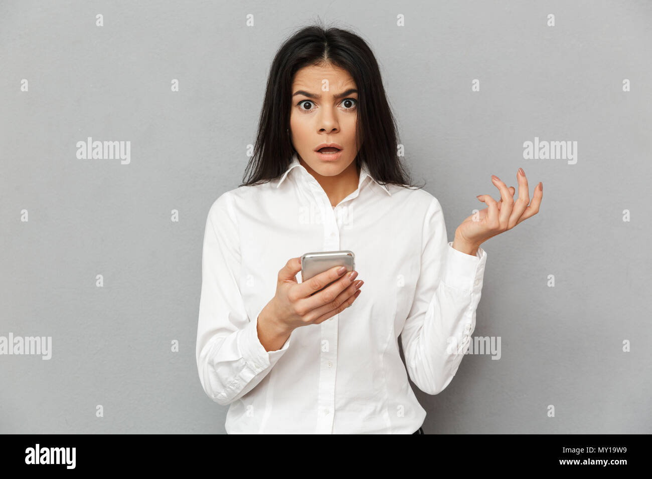 Photo of shocked or outraged woman 30s in formal wear looking on camera while holding smartphone in hand isolated over gray background - Stock Image