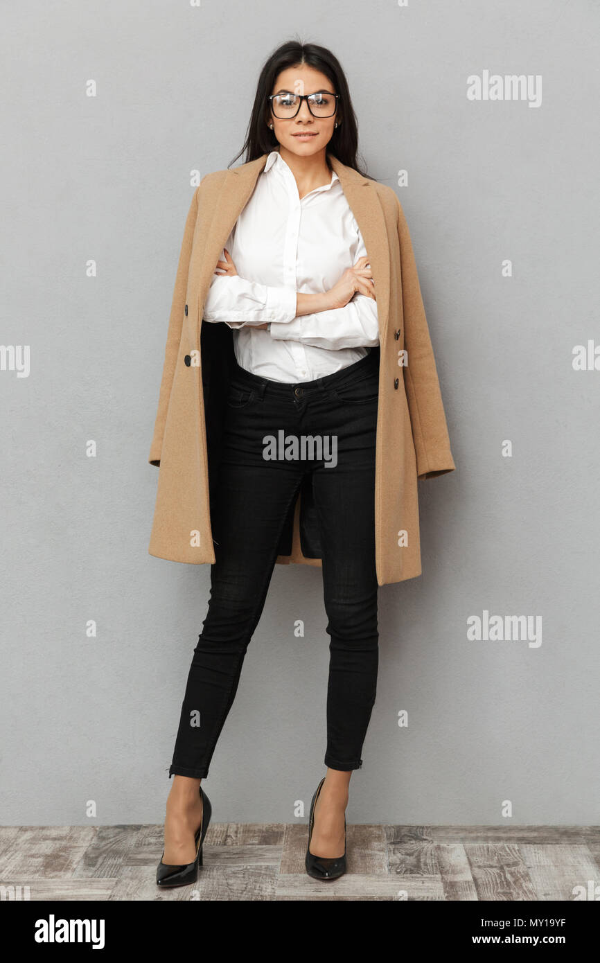 Full length image of elegant business woman in formal wear and beige coat posing at camera with hand folded isolated over gray background - Stock Image