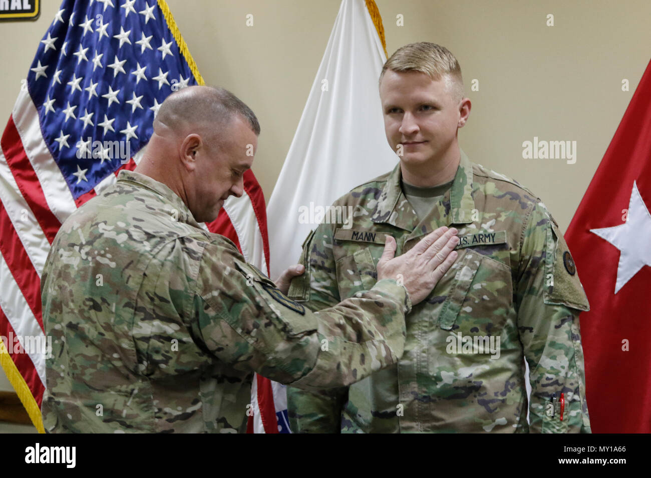 Brig. Gen. Robert D. Harter, 316th Sustainment Command (Expeditionary) commanding general, places the rank of 1st Lieutenant on Christopher Mann during a promotion ceremony at Camp Arifjan, Kuwait, Dec. 31, 2016. (U.S. Army Photo by Maj. Julius Penn) - Stock Image