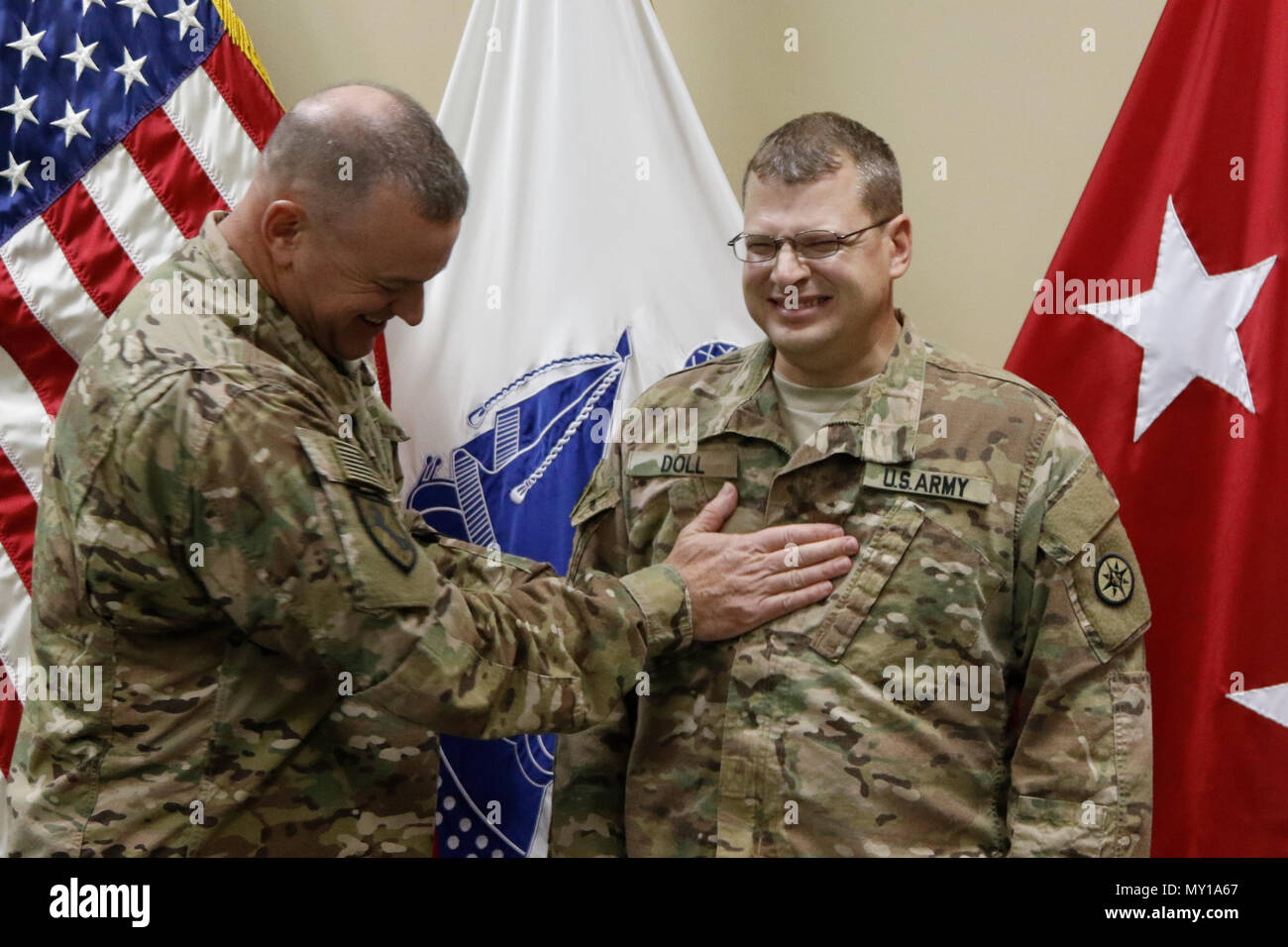 Brig. Gen. Robert D. Harter, 316th Sustainment Command (Expeditionary) commanding general, places the rank of Major on Phillip Doll during a promotion ceremony at Camp Arifjan, Kuwait, Dec. 31, 2016. (U.S. Army Photo by Maj. Julius Penn) - Stock Image