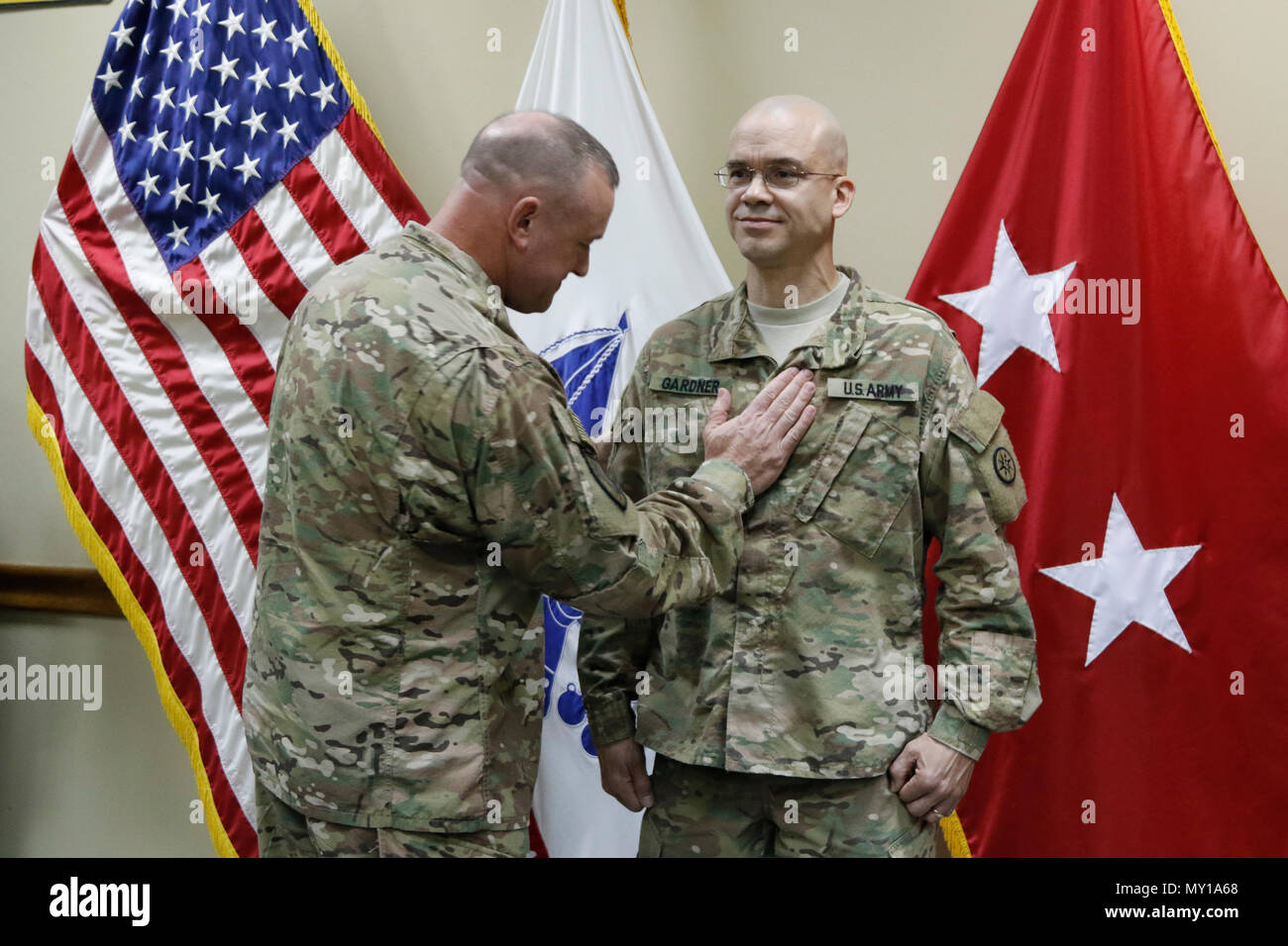 Brig. Gen. Robert D. Harter, 316th Sustainment Command (Expeditionary) commanding general, places the rank of Chief Warrant Officer 4 on Richard Gardner during a promotion ceremony at Camp Arifjan, Kuwait, Dec. 31, 2016. (U.S. Army Photo by Maj. Julius Penn) - Stock Image