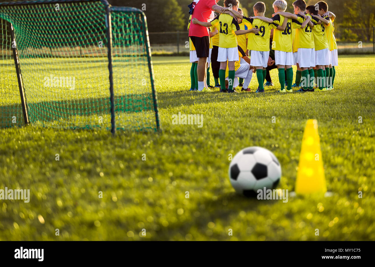 Soccer football training for young boys. Training session on the grass soccer field. Soccer ball and pylon cone and soccer goal in the foreground. You - Stock Image