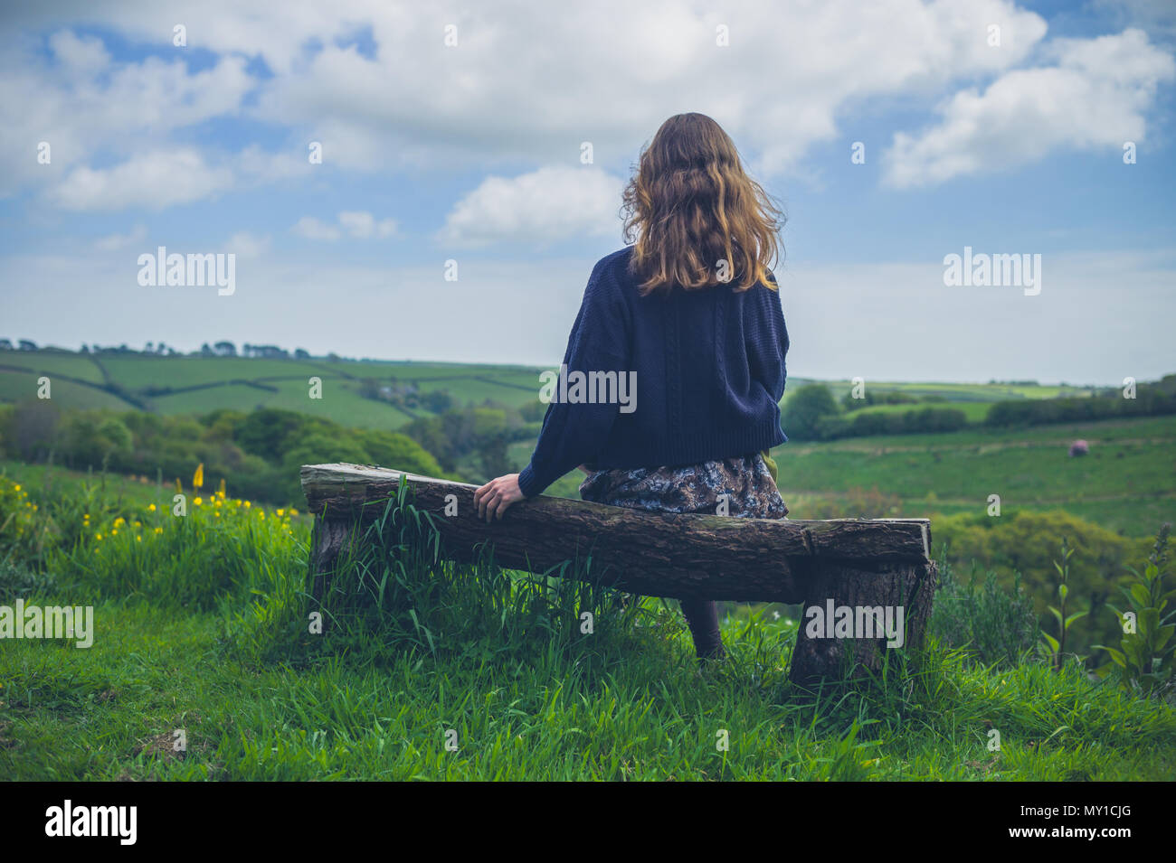A young woman is sitting on a bench in the countryside - Stock Image