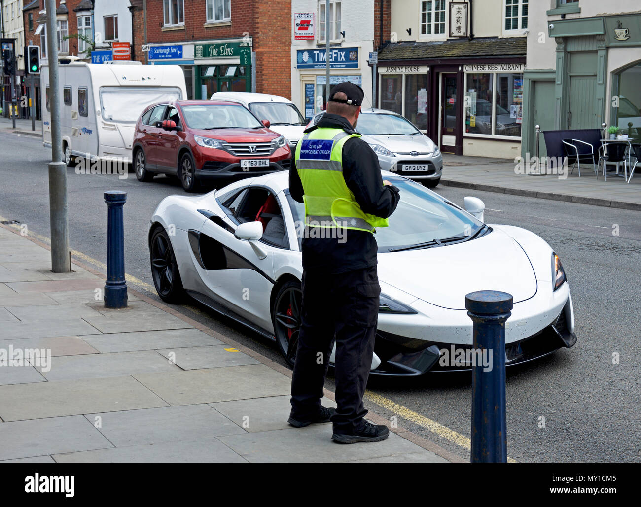 Traffic warden and sports car, parked on street, England UK - Stock Image