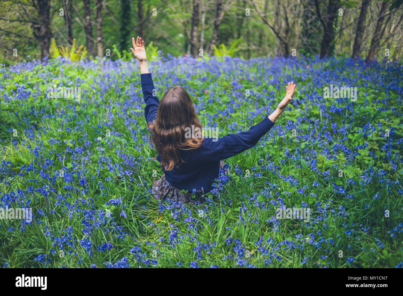 A young woman is sitting in a meadow of bluebells and is expressing joy by lifting her arms - Stock Image