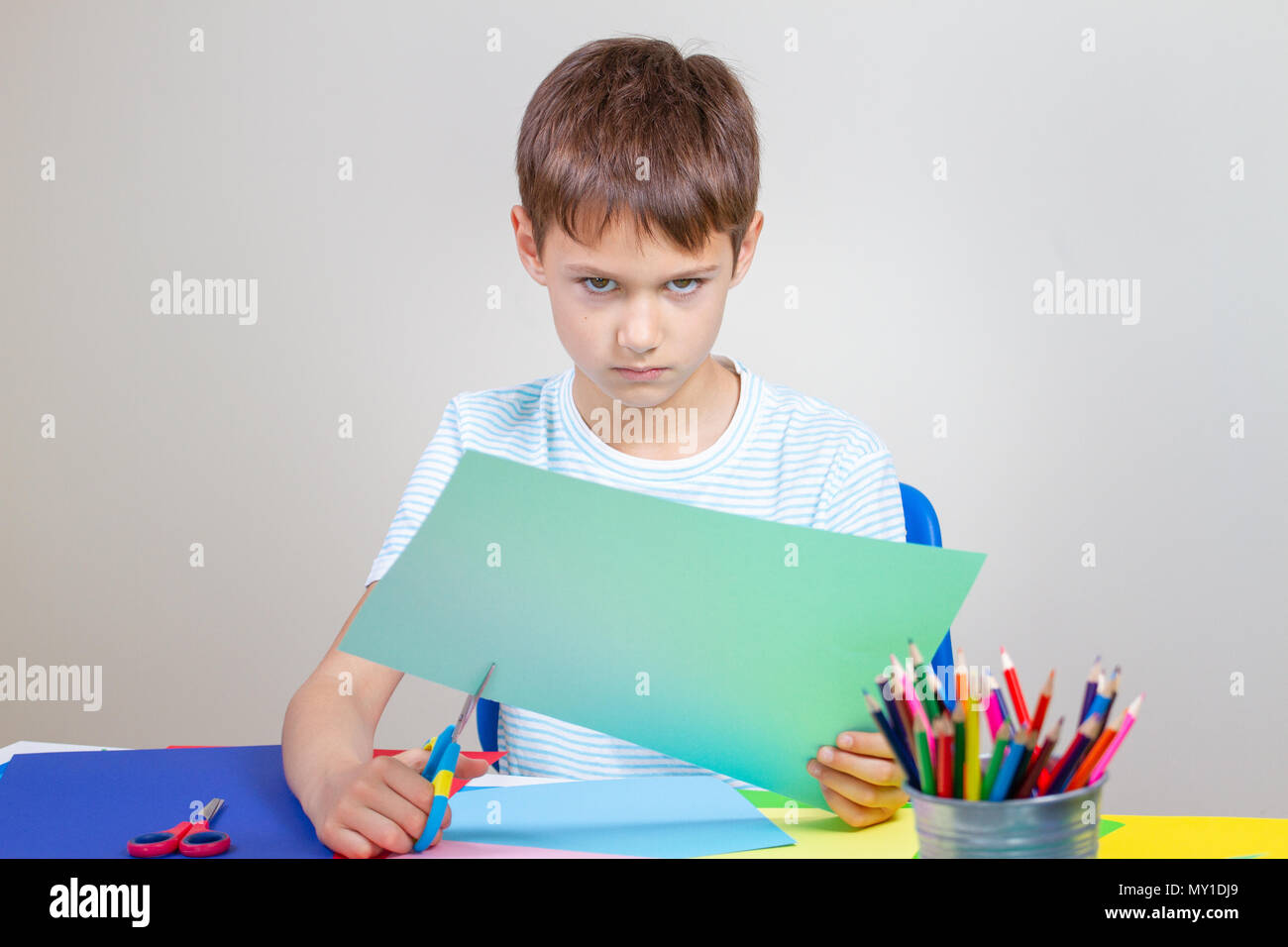 Angry child cutting colored paper with scissors at the table - Stock Image