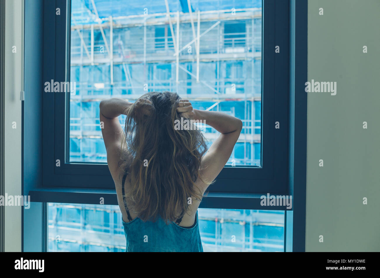 A young woman by the window in a high rise is annoyed by the building works outside - Stock Image
