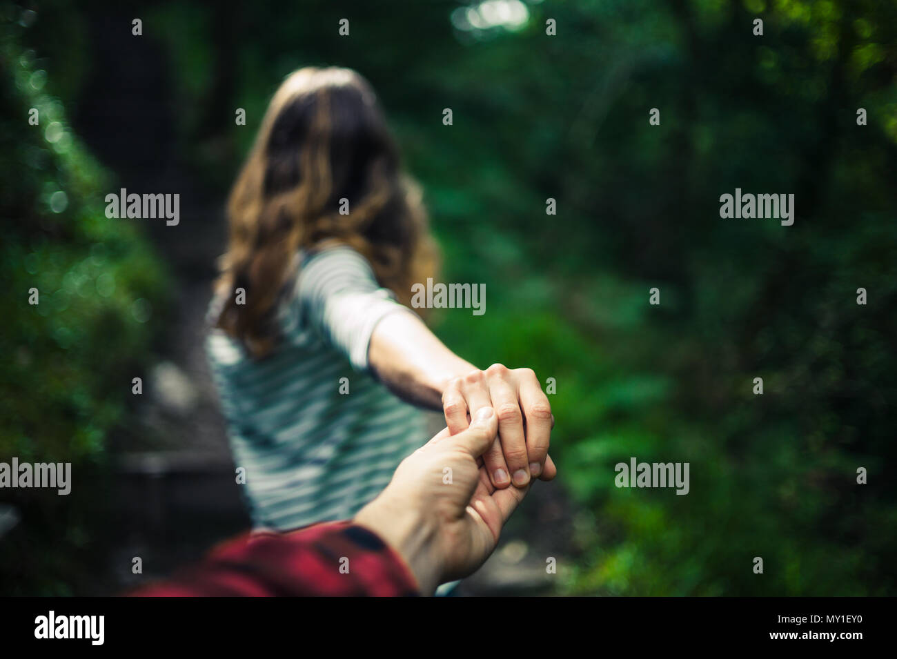 A young woman is guiding her boyfriend by the hand in a forest - Stock Image