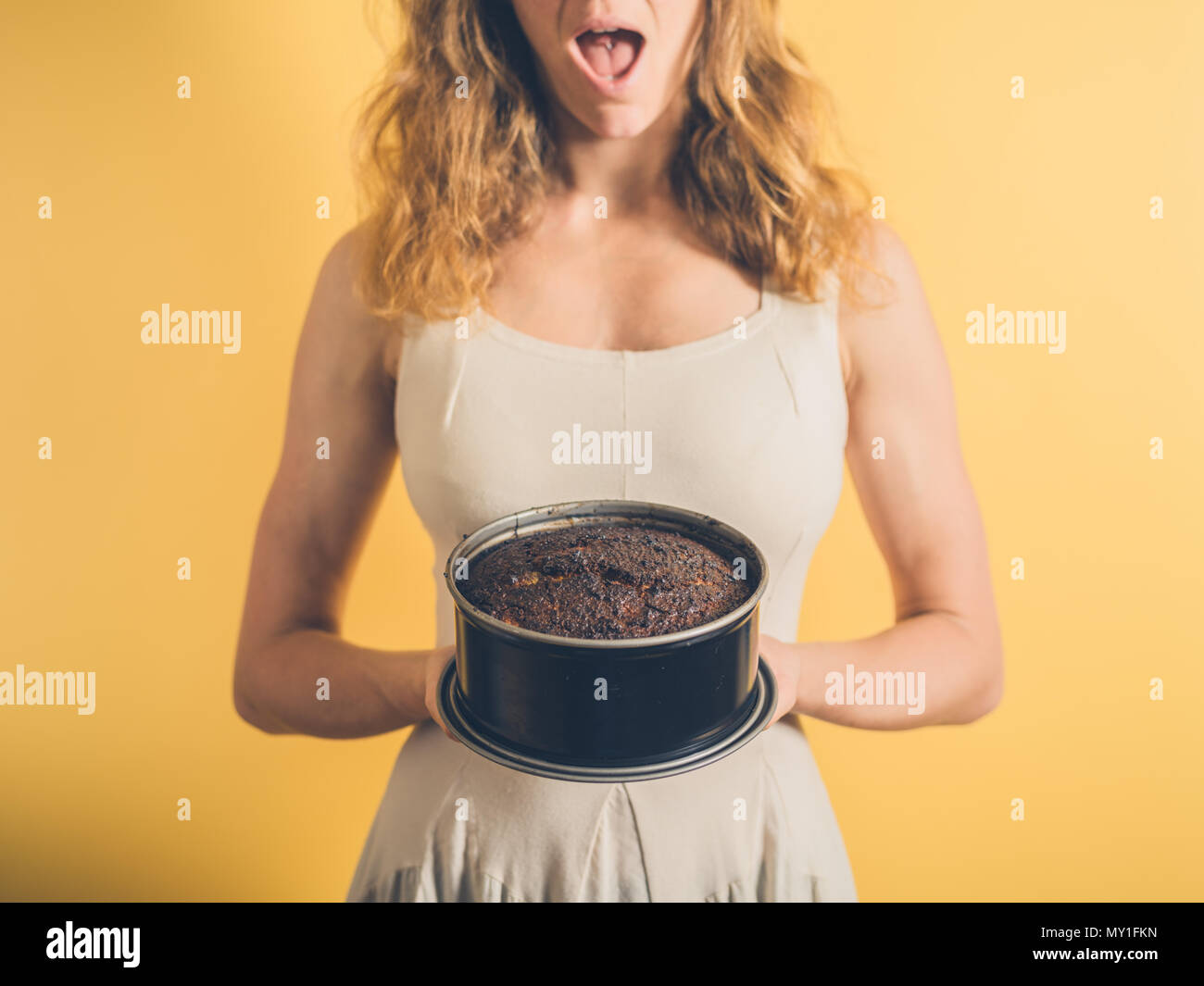 A surprised woman is holding a burnt cake - Stock Image