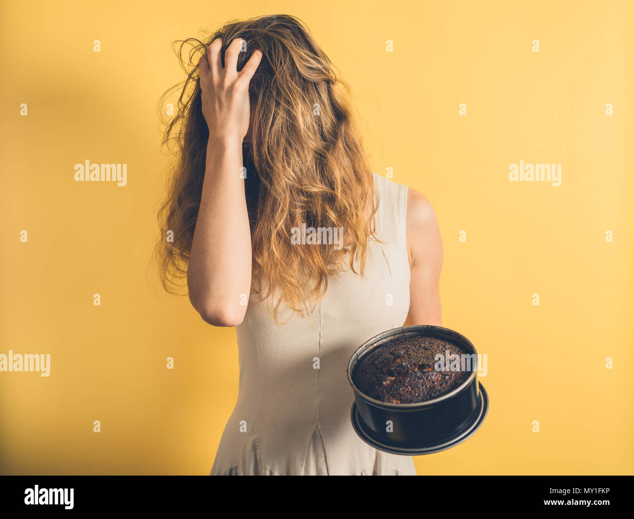 A young woman with a burnt cake is pulling her hair - Stock Image