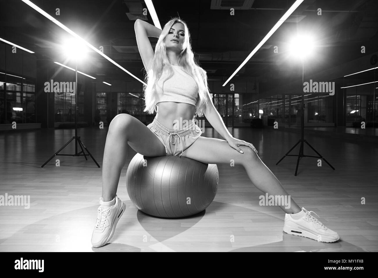 Blonde woman sitting on swiss ball - Stock Image