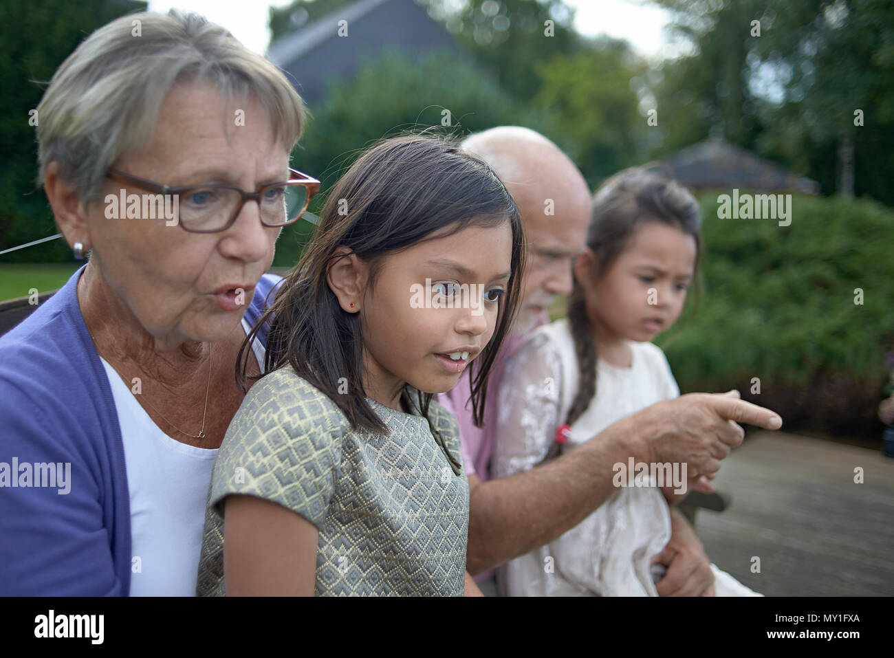 Family portrait of an elderly caucasian couple and their mixed race grandchildren in an unposed natural setting in the back yard in summer sunshine - Stock Image