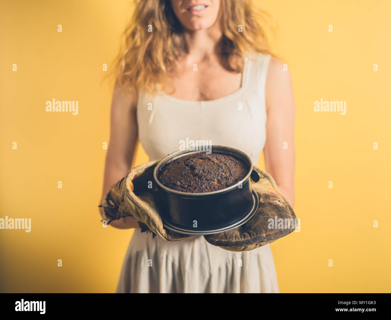 A young woman is holding a burnt cake with burnt oven gloves - Stock Image