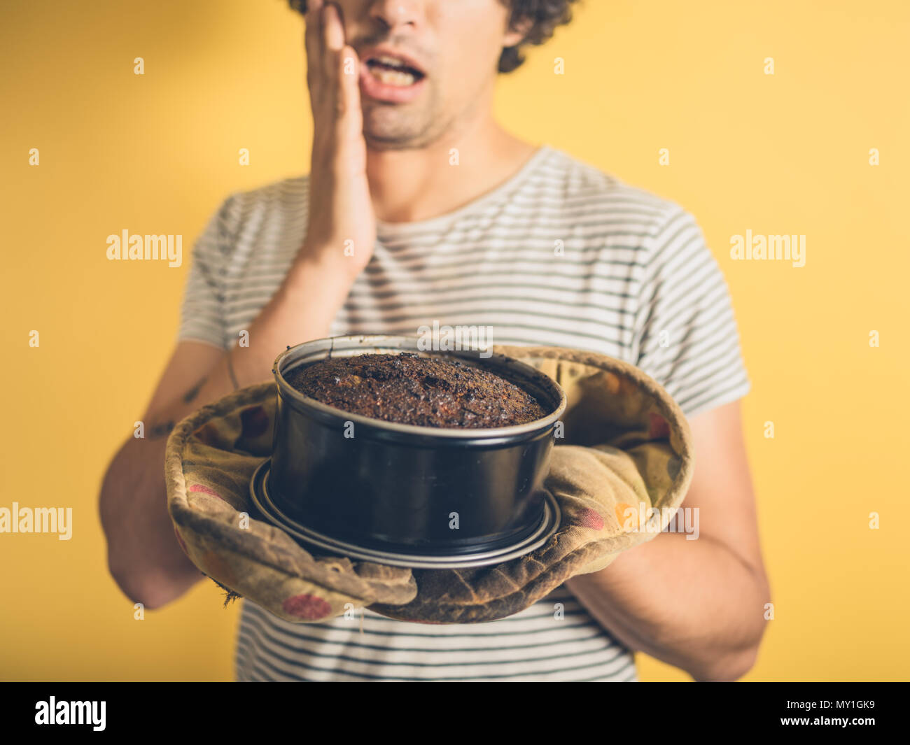 An upset young man is holding a burnt cake - Stock Image