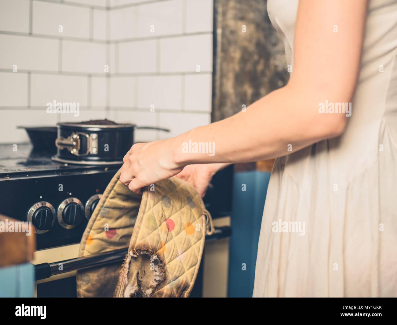A young woman is standing in the kitchen with a burnt cake and burnt oven gloves - Stock Image