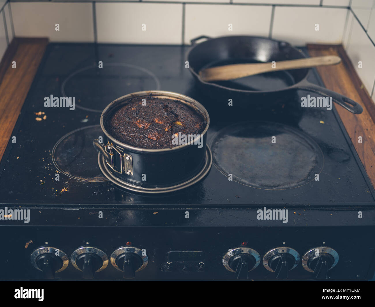 A burnt cake is sitting on a dirty stove - Stock Image