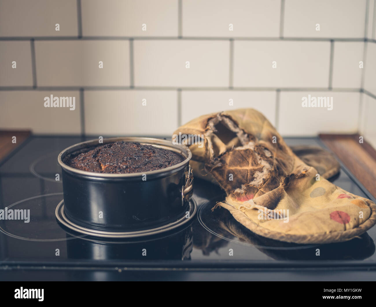 A burnt cake and a burnt oven glove on the cooker - Stock Image