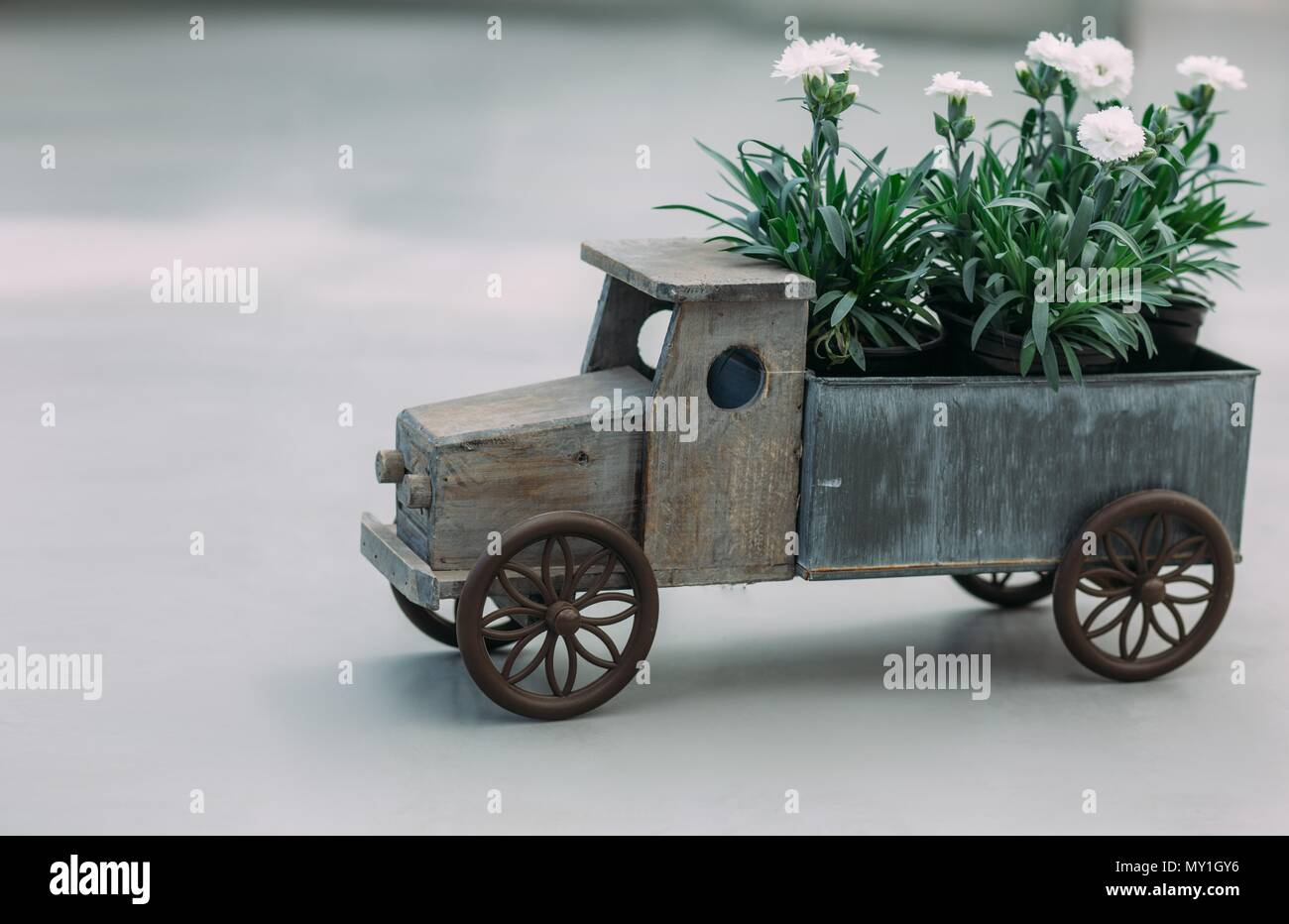 concept of flowers delivery, flowers in the carpet of a toy car - Stock Image