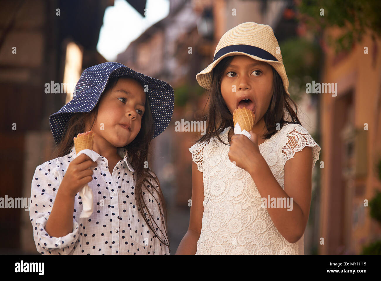 Two cute Asian sisters eating icecream together whilst on holiday in the Alsace region of France during summer - Stock Image