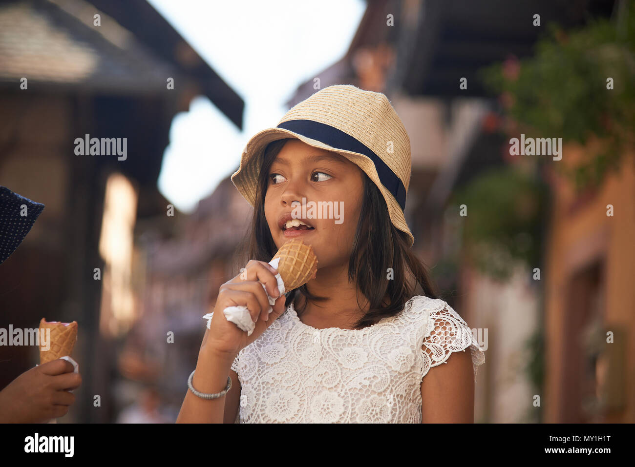 Little cute Asian girl wearing a straw hat eating icecream whilst on holiday in the Alsace region of France in summer sunshine on a hot day - Stock Image