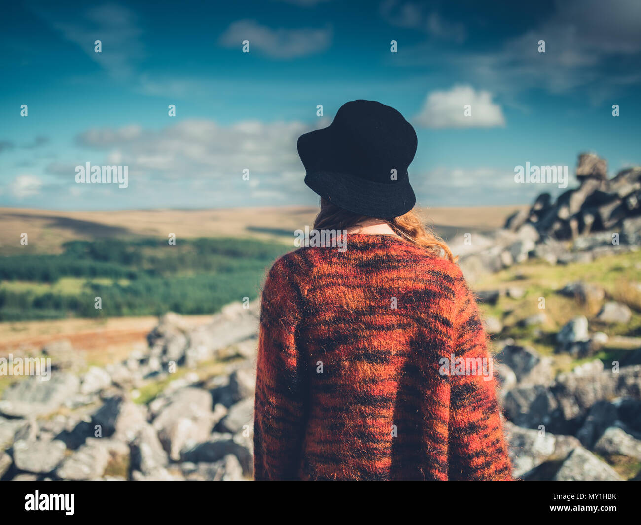 A young woman wearing a hat is walking in the wilderness - Stock Image