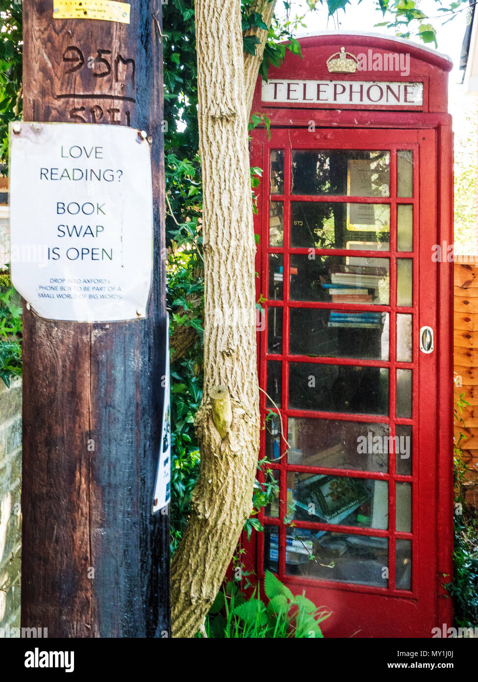 An old red telephone box used as a book swap location in a Wiltshire village. - Stock Image