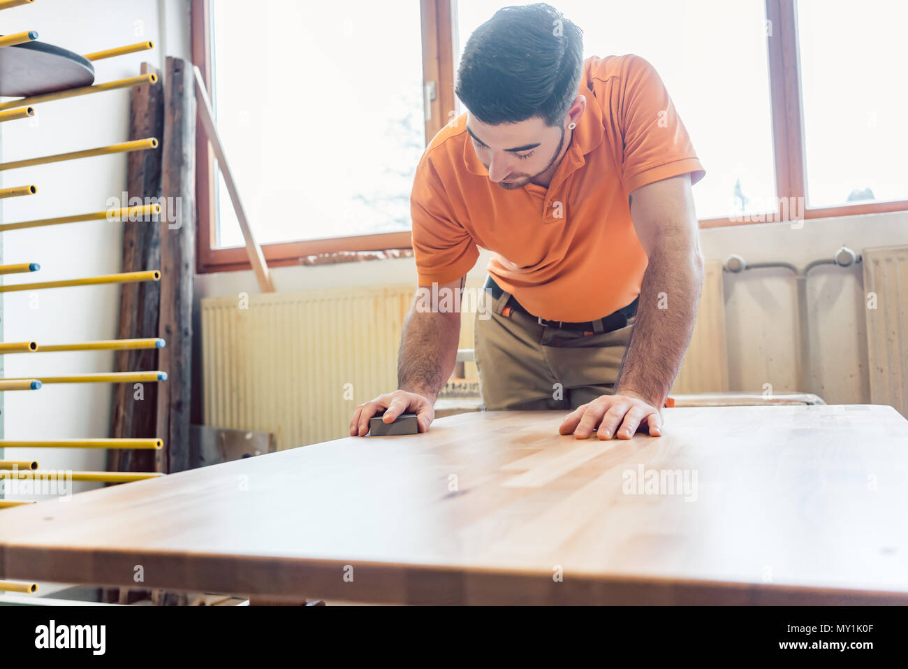 Carpenter polishing and varnishing a table - Stock Image