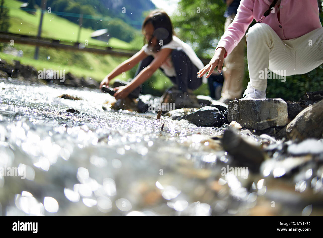 Two cute young girls playing together along a river stream high up in the Swiss mountains during a summer holliday in sunshine - Stock Image