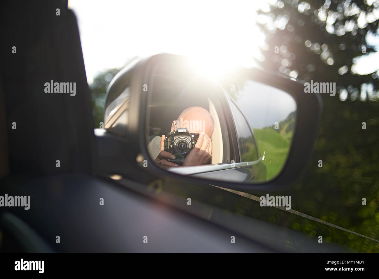 Close up of a photographer with a DSLR camera taking a photo of himself in the outside car mirror whilst sitting in the car on the way to the mountain Stock Photo