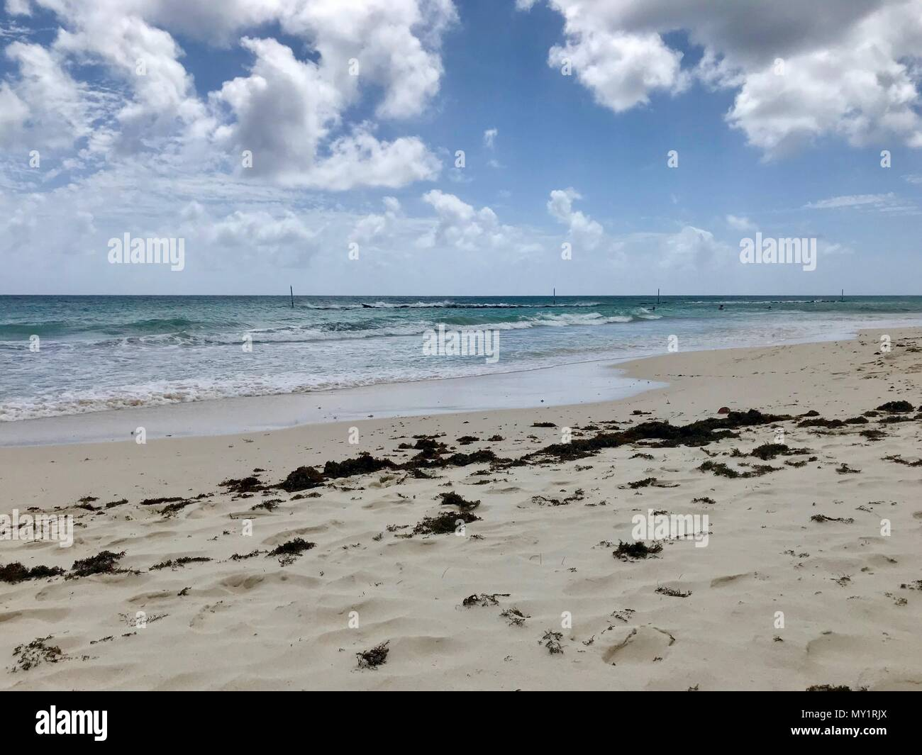 Idyllic and beautiful beach in Barbados (Caribbean island): Nobody, white sand, turquoise water, waves and white clouds Stock Photo