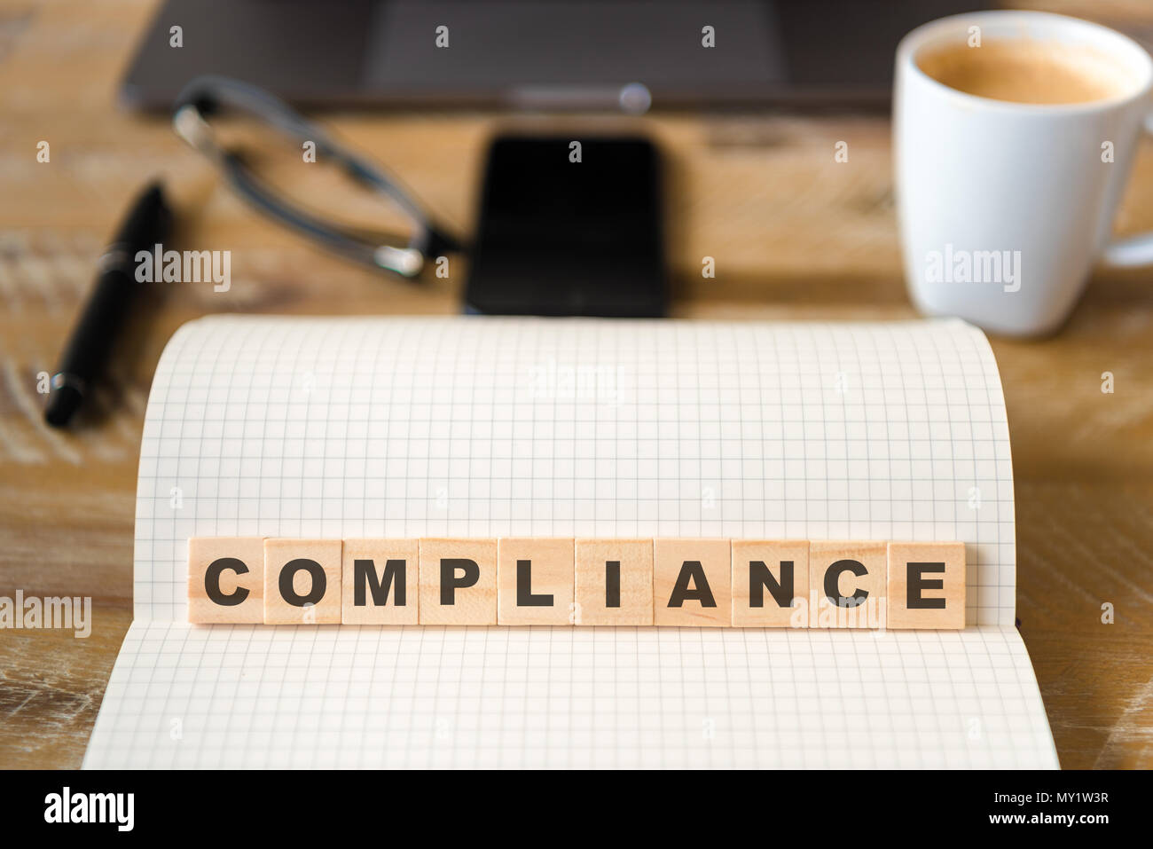 Closeup on notebook over wood table background, focus on wooden blocks with letters making Compliance text. - Stock Image