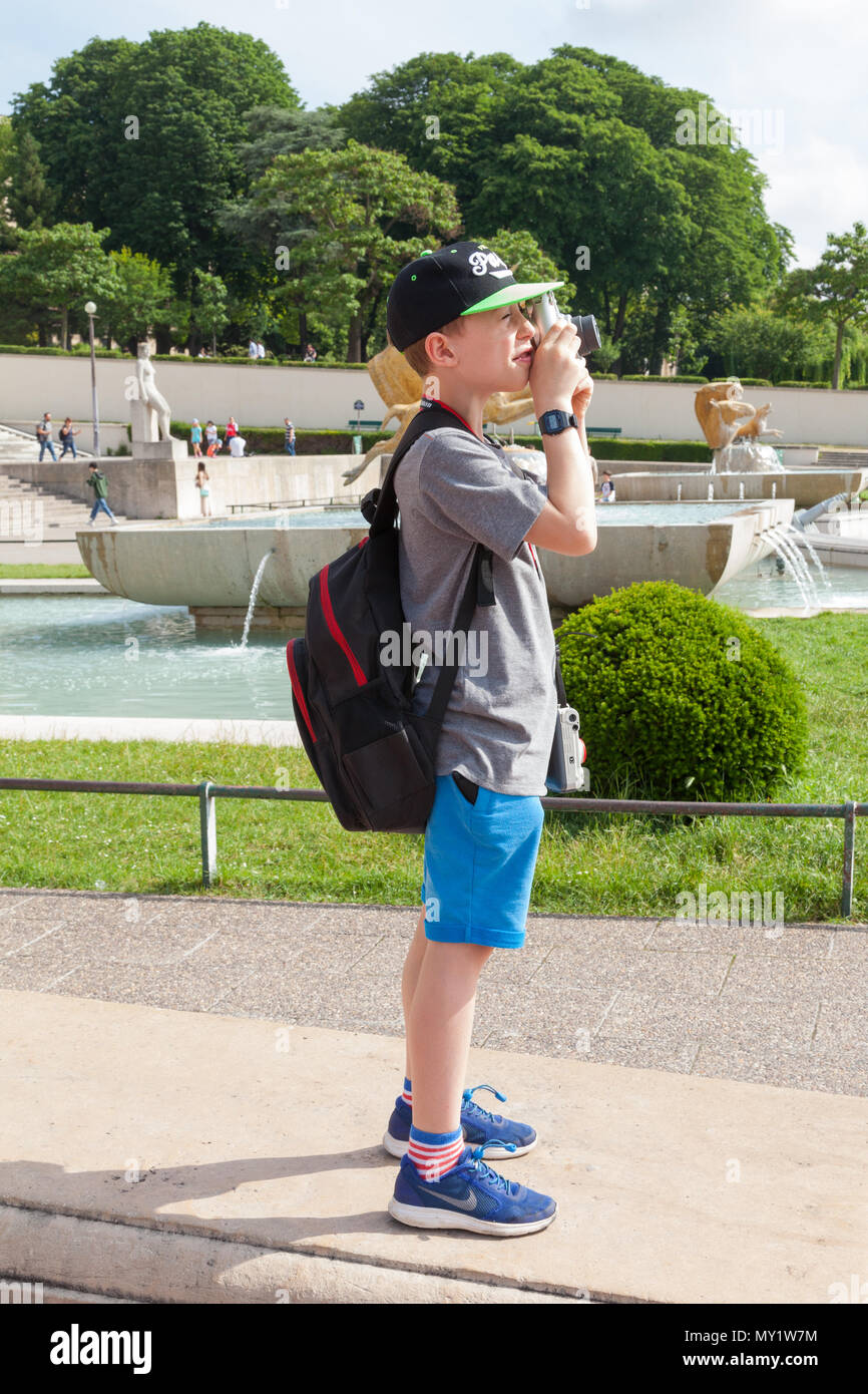 Nine year old boy taking a instant photo at the Trocadero, Paris, France. - Stock Image